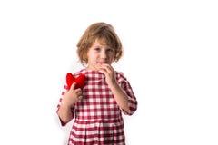 Смешной ребенок девушки в красном платье шотландки с красным вязать крючком крючком сердцем, Стоковые Фотографии RF