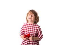 Смешной ребенок девушки в красном платье шотландки с красным вязать крючком крючком сердцем, Стоковые Изображения