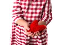 Смешной ребенок девушки в красном платье шотландки с красным вязать крючком крючком сердцем, Стоковая Фотография RF