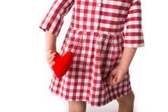Смешной ребенок девушки в красном платье шотландки с красным вязать крючком крючком сердцем, Стоковые Фото