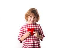 Смешной ребенок девушки в красном платье шотландки с красным вязать крючком крючком сердцем, Стоковое Изображение