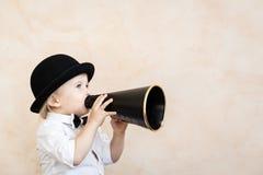 Смешной ребенок играя с черным ретро мегафоном стоковые фотографии rf