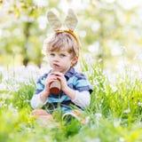 Смешной ребенок нося уши зайчика пасхи и есть шоколад на sp Стоковая Фотография