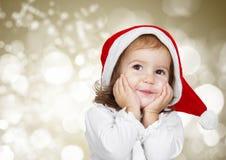 Смешной ребенок одел шляпу santa, на золотой предпосылке bokeh Стоковая Фотография