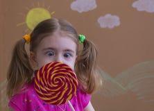 Смешной ребенок с леденцом на палочке конфеты, счастливая маленькая девочка есть большой леденец на палочке сахара, ребенк ест по Стоковые Фото