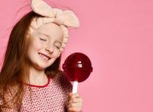 Смешной ребенок с леденцом на палочке конфеты, счастливая маленькая девочка есть большой леденец на палочке сахара стоковое изображение