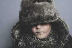 Смешной ребенок с меховой шапкой и зима покрывают, холодная концепция и шторм Стоковые Изображения