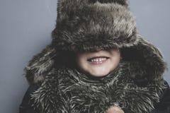 Смешной ребенок с меховой шапкой и зима покрывают, холодная концепция и шторм Стоковая Фотография RF