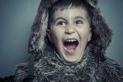 Смешной ребенок с меховой шапкой и зима покрывают, холодная концепция и шторм Стоковые Изображения RF