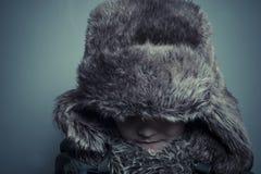 Смешной ребенок с меховой шапкой и зима покрывают, холодная концепция и шторм Стоковое Фото