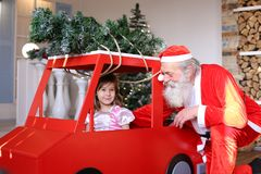 Смешной Санта Клаус играя при маленькие принцы развевая рука в красном цвете стоковые изображения