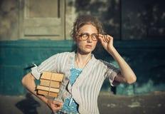 Смешной студент девушки с книгами в стеклах и винтажном платье Стоковые Изображения RF