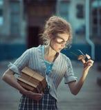 Смешной студент девушки с книгами и стеклами и винтажным платьем Стоковое Изображение