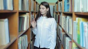 Смешной сумасшедший студент девушки со стеклами имея потеху в библиотеке Женщина околпачивая вокруг в библиотеке видеоматериал