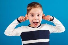 Смешной счастливый молодой мальчик в свитере показывая гримасу на камере стоковая фотография