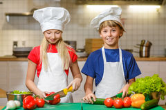 Смешной счастливый мальчик и девушка шеф-повара варя на Стоковая Фотография RF
