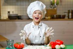 Смешной счастливый мальчик шеф-повара варя на кухне ресторана Стоковые Изображения