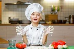 Смешной счастливый мальчик шеф-повара варя на кухне ресторана Стоковая Фотография RF