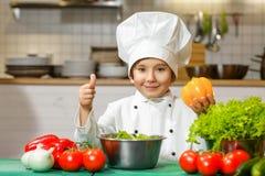 Смешной счастливый мальчик шеф-повара держа болгарский перец или Стоковые Фотографии RF