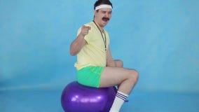Смешной тренер человека с усиком от 80's, на шарике фитнеса на голубой предпосылке медленном mo видеоматериал