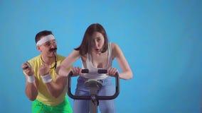 Смешной тренер человека 80's с поездами усика молодая женщина на велотренажере на голубой предпосылке медленном mo акции видеоматериалы