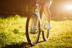 Смешной управлять девушки внешний Фокус на велосипеде Солнечная концепция образа жизни лета Женщина в платье и шляпе в поле с Стоковое Изображение RF