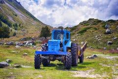Смешной усмехаясь трактор расположенный на травянистом glade в горах Стоковое Фото