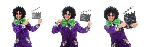 Смешной человек в парике при нумератор с хлопушкой изолированный на белизне Стоковое Фото