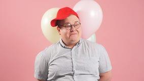 Смешной человек очень подобный Winnie the Pooh с воздушными шарами изолированными над пинком акции видеоматериалы