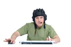 Смешной человек в шлеме танка и сигара играя в игре, сидя фронте компьютера белизна изолированная предпосылкой Стоковая Фотография RF