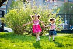 Смешные девушки идя на лужайку с ее матерью Сестры играют вместе с мамой материнская забота E стоковая фотография rf