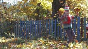 Смешные дети имеют потеху играя и скача с кленовыми листами в парке осени видеоматериал