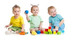 Смешные дети собирают играть красочные игрушки изолированные на белизне стоковая фотография