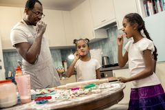 Смешные дочери и отец пробуя некоторое салями пока варящ пиццу стоковые изображения