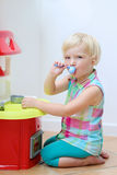 Смешные игры девушки preschooler с кухней игрушки Стоковое фото RF