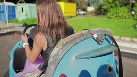 Смешные любящие автомобили езды парня и девушки электрические в парке атракционов видеоматериал