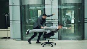 Смешные молодые люди имеют потеху со стулом завальцовки, одно нажимает кресло другое лежит в нем и двигает вперед внутри акции видеоматериалы