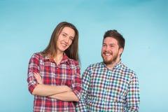 Смешные молодые пары смеясь и околпачивая вокруг совместно на голубой предпосылке стоковые фото