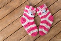 Смешные носки младенца на предпосылке деревянного стола Стоковые Фото