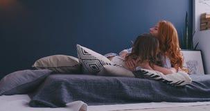 Смешные осчастливленные сестры имея потеху на выходных лежа в кровати в утре на мягкий смеяться подушек чувствуют счастливыми, ма видеоматериал