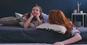 Смешные осчастливленные сестры имея потеху на выходных лежа в кровати в утре на мягкий смеяться подушек чувствуют счастливыми, ма акции видеоматериалы