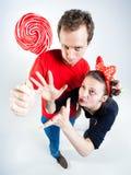 Смешные пары играя с леденцом на палочке в студии Стоковое фото RF