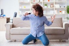 Смешные песни петь человека в караоке дома стоковое изображение