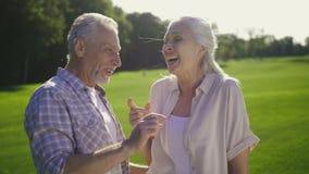 Смешные пожилые пары смеясь над на шутке outdoors акции видеоматериалы