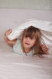 Смешные сестры отпрысков девушки играя на кровати с подушками Стоковые Изображения