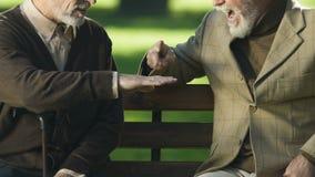 Смешные старики играя игру утес-бумаг-ножниц, flicking лоб, имеющ потеху видеоматериал