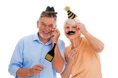 Смешные старшие пары держа шляпы и усики партии на ручках стоковое фото rf