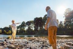 Смешные старшие пары играя с водой на реке в солнечном дне стоковое фото