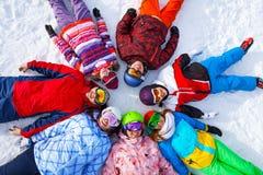 Смешные счастливые snowboarders лежа в круге Стоковое фото RF