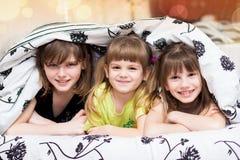 Смешные тайники маленьких сестер под одеялом стоковые фото